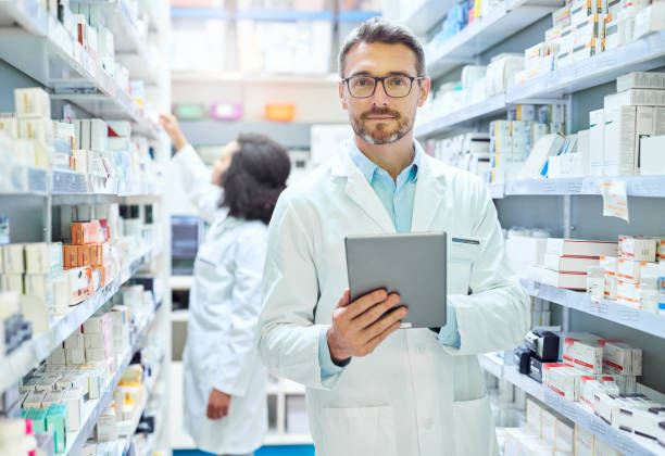 It's a pharmacist's best friend Shot of a mature man using a digital tablet to do inventory in a pharmacy pharmacist stock pictures, royalty-free photos & images