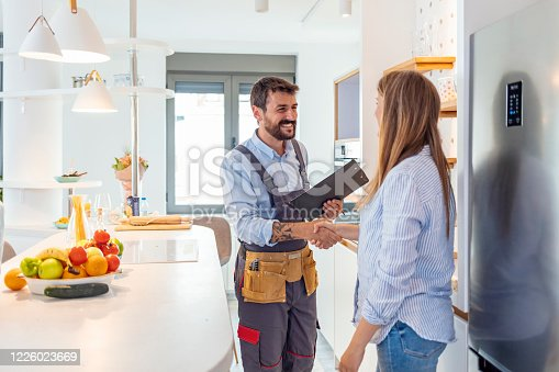Young Woman Shaking Hands To Male Plumber With Clipboard In Kitchen Room