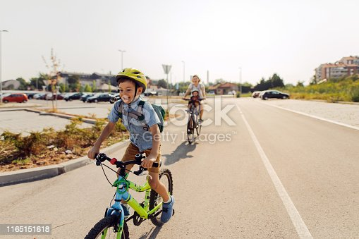 Smiling boy commute to school with mom and baby brother by bicycles