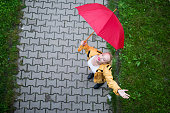 Young girl holding umbrella while walking outdoors.