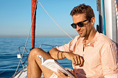 Shot of a handsome young man reading a book on a relaxing boat cruise