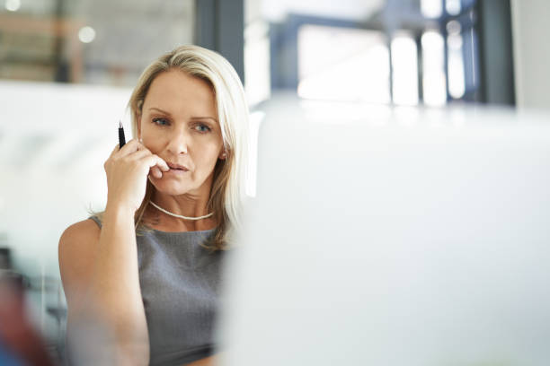 It's a risky decision but is it worth it? Shot of a mature businesswoman using a laptop in a modern office and looking thoughtful decisions stock pictures, royalty-free photos & images