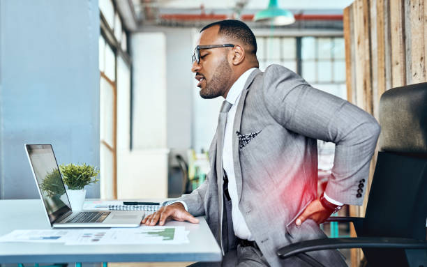 It's a sign of too much stress with little rest Shot of a young businessman suffering with back pain while working in an office bad posture stock pictures, royalty-free photos & images