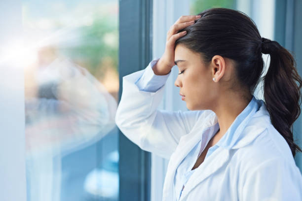 It's a stressful profession Shot of a young female doctor looking stressed out while standing at a window in a hospital mental burnout stock pictures, royalty-free photos & images