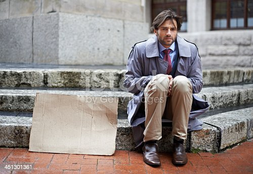 View of an unemployed businessman sitting on the steps begging for work