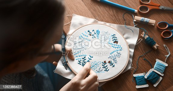 Cropped shot of an unrecognizable woman doing embroidery at home