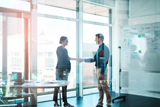 It's a win for you and a win for me Shot of a businessman and businesswoman shaking hands in a modern office outsourcing stock pictures, royalty-free photos & images