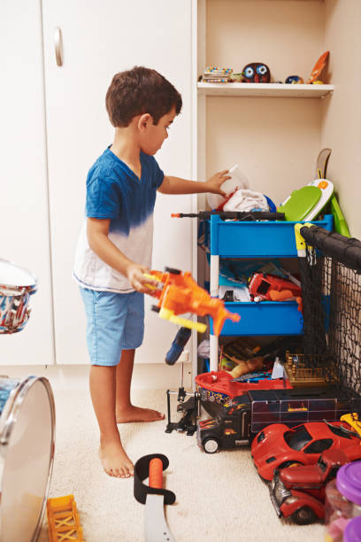 It's about time I pack my toys away Shot of a focused young little boy packing toys away and tidying her room at home kids cleaning up toys stock pictures, royalty-free photos & images