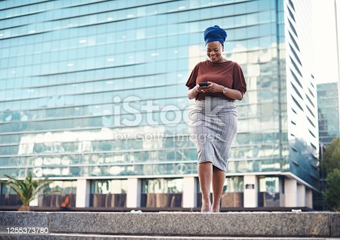 Shot of a young businesswoman using a smartphone against a city background
