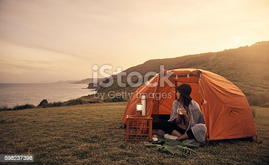 Shot of a young female camper sitting at her camp site