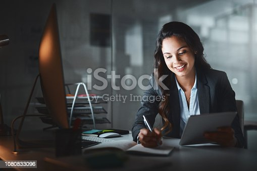 Shot of a young businesswoman using a digital tablet while working late in a modern office