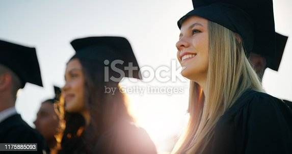 Cropped shot of a group of cheerful young students standing together on graduation day outside during the day