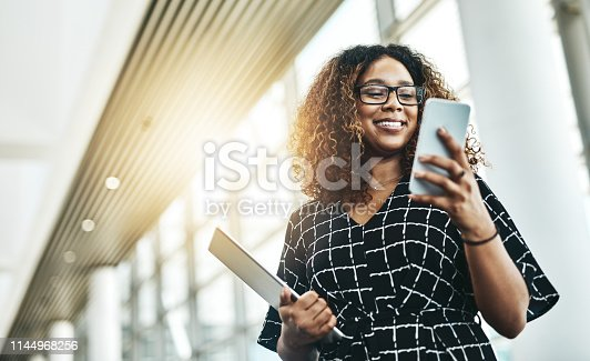 Low angle shot of an attractive young businesswoman using a smartphone in a modern office