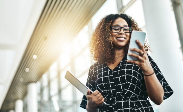 It's all easier when done digitally Low angle shot of an attractive young businesswoman using a smartphone in a modern office african american ethnicity stock pictures, royalty-free photos & images