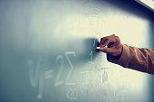 Cropped image of a teacher writing a formula on a blackboardhttp://195.154.178.81/DATA/istock_collage/0/shoots/782800.jpg