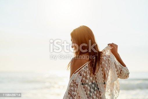 Shot of a beautiful young woman spending the day at the beach