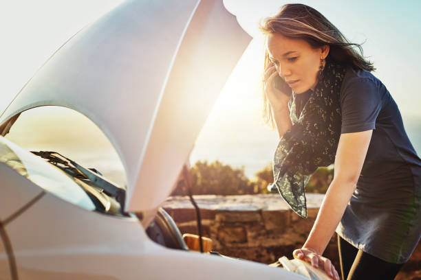 It's an emergency - please come quickly Cropped shot of a young woman calling roadside assistance after breaking down aground stock pictures, royalty-free photos & images