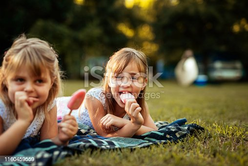Sisters eating an icecream while enjoying time together.