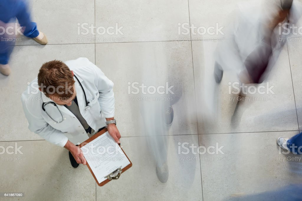 It's another busy day at the hospital High angle shot of a male doctor looking at a patient's file in a busy hospital 20-29 Years Stock Photo