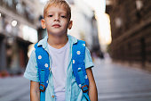 Portrait shot of a young blond boy posing for a photo on the first day of school