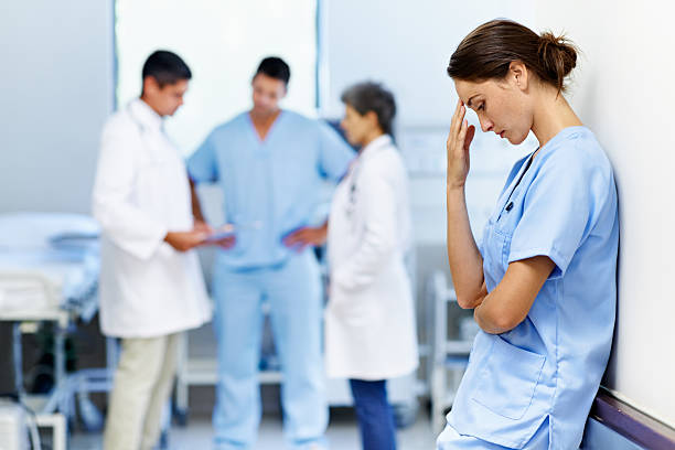 It's been a long shift Shot of an exhausted doctor leaning against a wall with colleagues in the backgroundhttp://195.154.178.81/DATA/i_collage/pu/shoots/804719.jpg distraught stock pictures, royalty-free photos & images