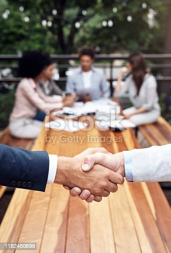 Cropped shot of two unrecognizable businessmen shaking hands while their colleagues sit behind them outdoors