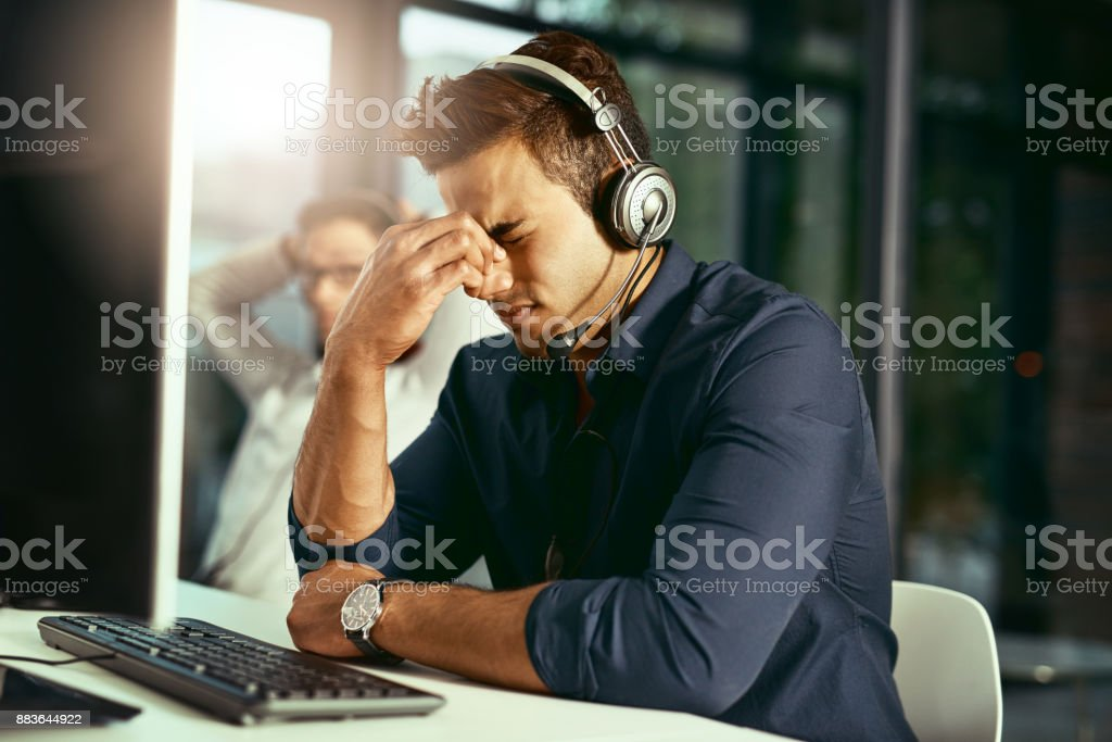 It's been a stressful day at work Shot of a young call centre agent looking stressed out while working in an office Adult Stock Photo