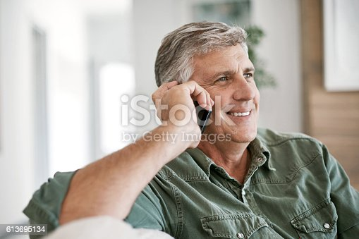 Cropped shot of a mature man talking on a cellphone at home