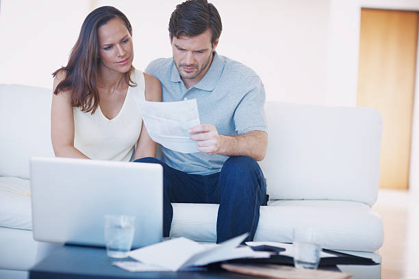 It's budgeting time again... A young couple discussing their home finances and inspecting bills while sitting together in their living room alongside stock pictures, royalty-free photos & images