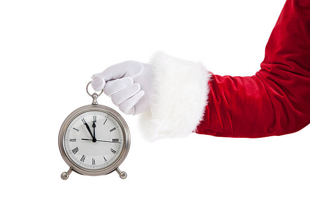 It's Christmas Time As Santa Holds A Clock stock photo