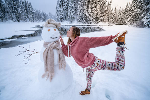 It's Christmas time - woman posing with snowman on winter vacations stock photo