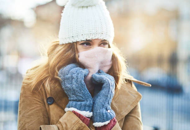 It's cold out here, I have to cover up Shot of an attractive young woman enjoying being out in the snow warm clothing stock pictures, royalty-free photos & images