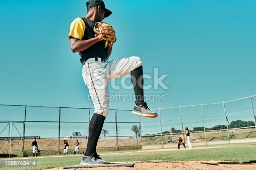 shot of a young baseball player getting ready to pitch the ball during a game outdoors