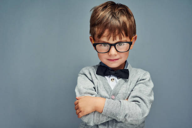 It's cool to be clever Studio portrait of a smartly dressed little boy posing confidently against a gray background child prodigy stock pictures, royalty-free photos & images