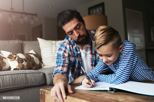 Shot of a father helping his little son with his homework