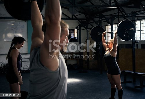 Cropped shot of a group of young athletes working out in the gym