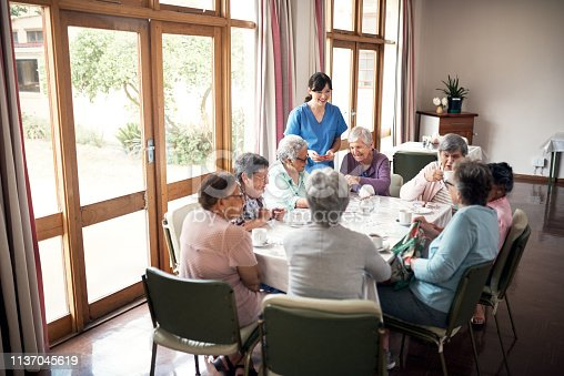 Shot of a group of senior women playing cards together at a retirement home