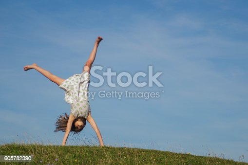 A young girl happily cartwheels on a sunny summer's day with a blue sky backdrop.