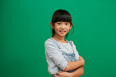 Studio portrait of confident little girl standing with her arms folded against a green background