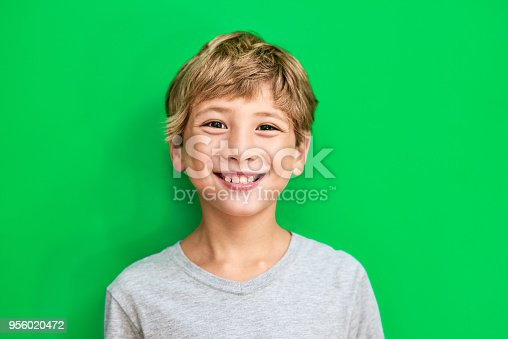 Studio portrait of a young boy standing against a green background