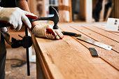 Cropped shot of an unrecognizable carpenter hammering nails on wood inside a workshop