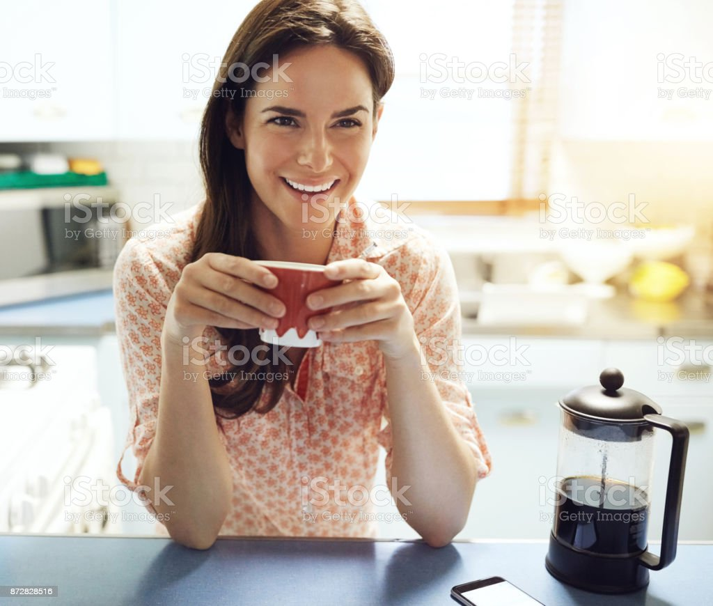 Shot of an attractive young woman having a cup of coffee at home