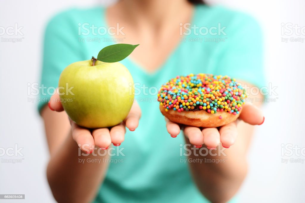 It's hard to choose healthy food concept, with woman hand holding an green apple and a calorie bomb donut royalty-free stock photo