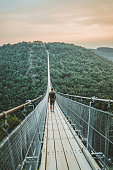 Photo of young Man walking on a hanging bridge in Germany during the summer day, Geierlay, The longest pedestrian bridge in Germany, suspension swing bridge. Young Man standing alone outdoor and admiring view Travel Lifestyle concept with rope bridge background and sunset.