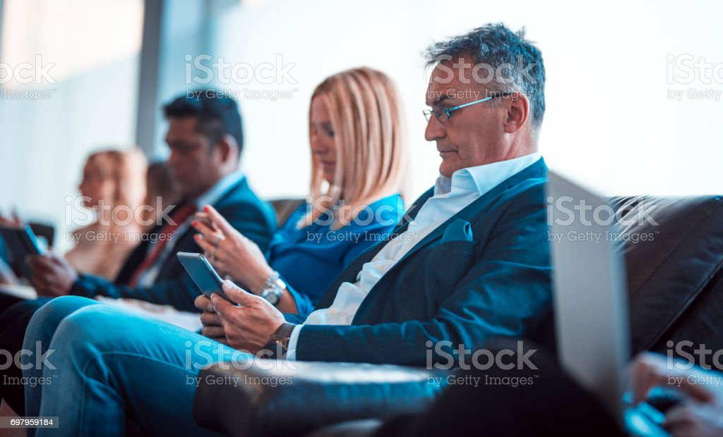 It's hard to wait for a long time Group of business people sitting and waiting for job interview. They are using mobile phones and digital tablets. Adult Stock Photo