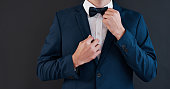 Cropped shot of an unrecognizable bridegroom adjusting his bowtie in preparation for his wedding