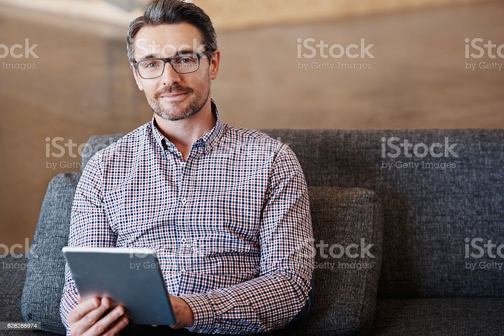 Portrait of a mature businessman working on a digital tablet in an...