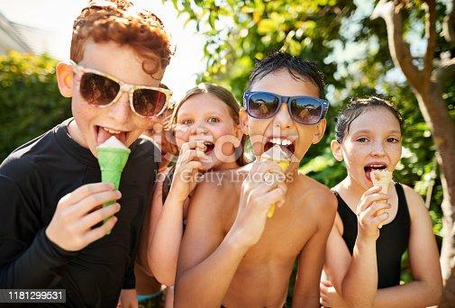 Group of cute little kids enjoying having ice cream outdoors
