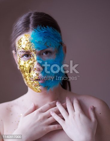 It's important to distinguish. Beautiful woman with glitter and fathers. Close up.