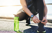 Closeup shot of an unidentifiable man tying his laces while exercising outdoors
